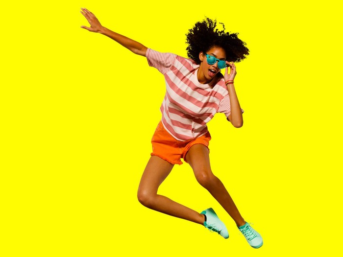 A woman wearing Snap Spectacles on a yellow background.