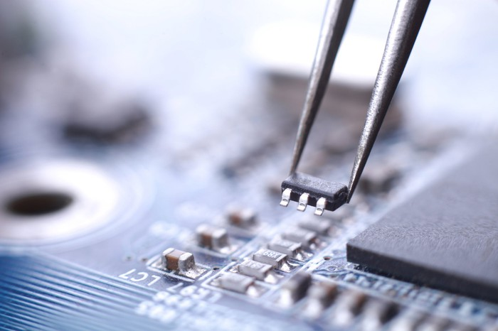 Close-up shot of a small microchip being placed on a circuit board with the help of tweezers.