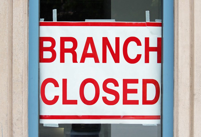 """Sign that reads """"branch closed"""" in a bank window."""