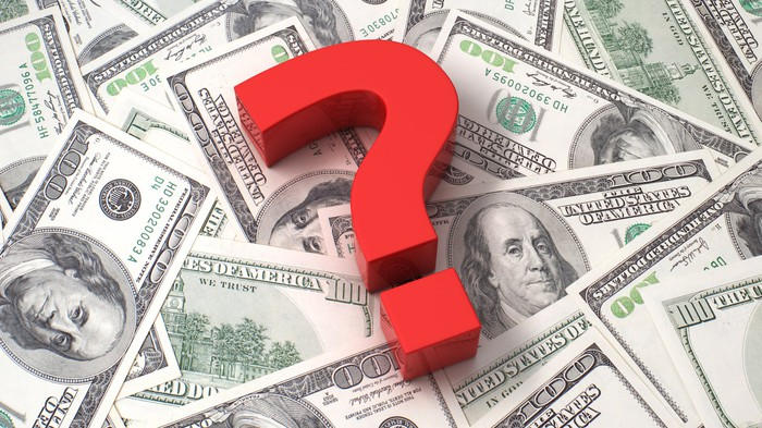 A big red question mark on top of hundred dollar bills.