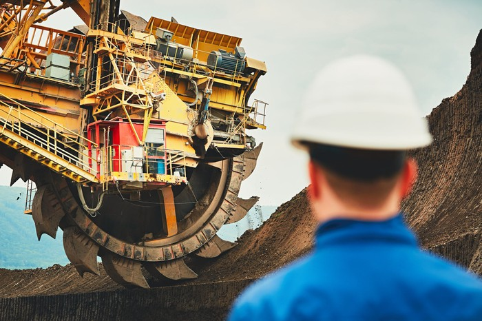 A man watching mining equipment at work