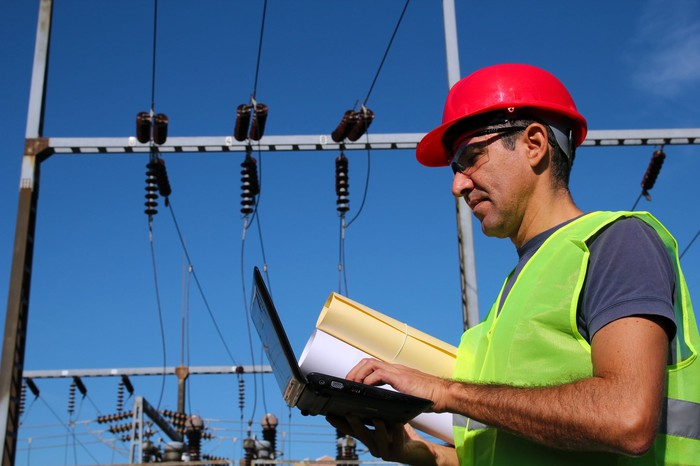 A man with high voltage power equipment behind him
