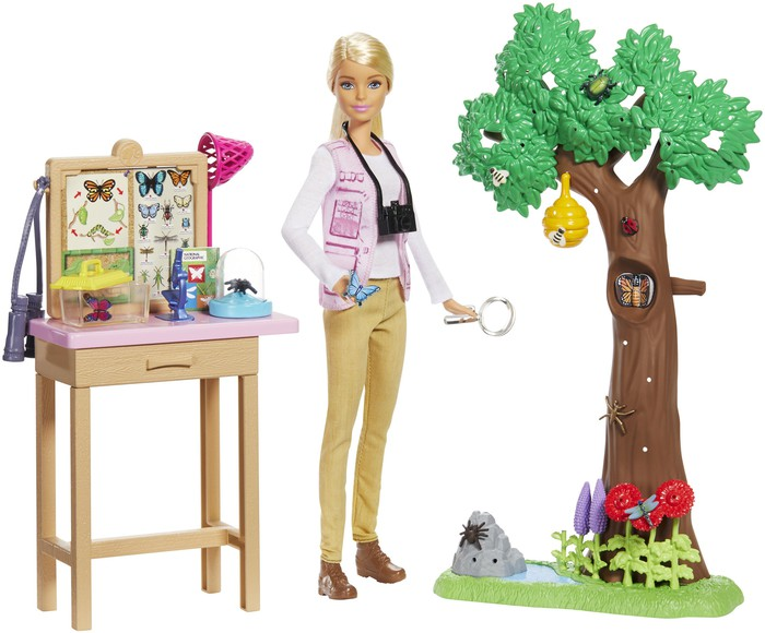 Barbie as part of a play set featuring a tree on one side and a butterfly collection on a table on the other.