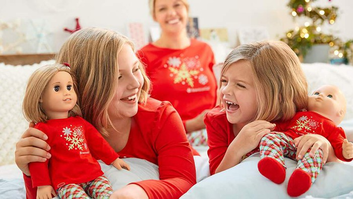 Two girls holding dolls in front of their mother, all three of them wearing matching red holiday pajamas, laughing and smiling on Christmas morning.