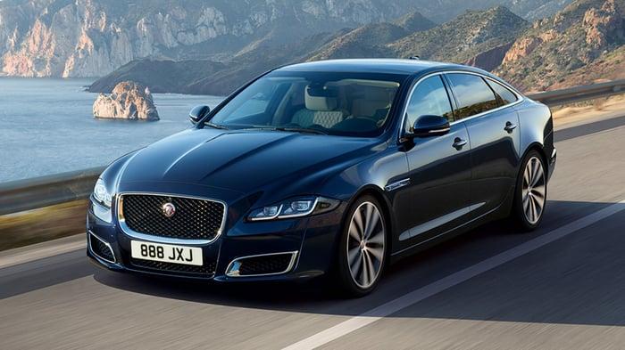 Dark-colored Jaguar on a road in front of a seaside landscape.