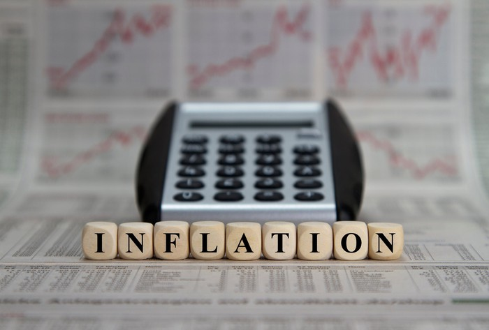 """Inflation"" spelled out with Scrabble pieces and a calculator."