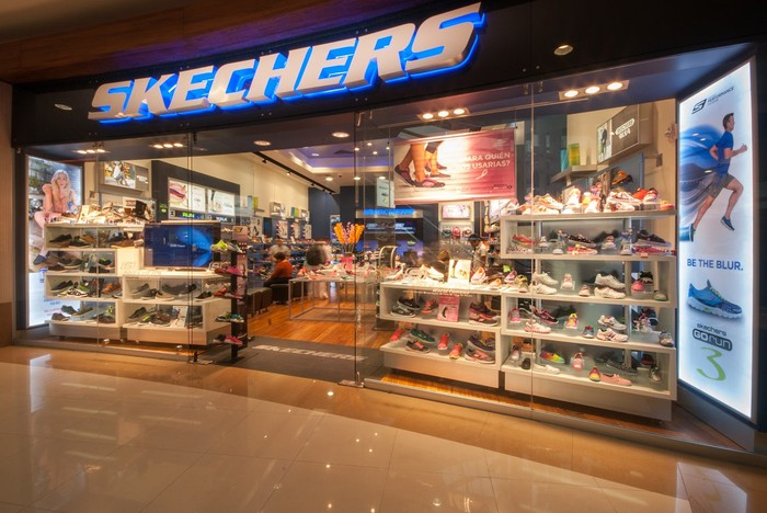 Skechers retail store as seen from outside, with lots of shoe displays.