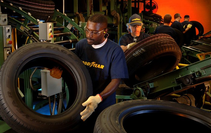 Two workers wearing Goodyear t-shirts with tires.