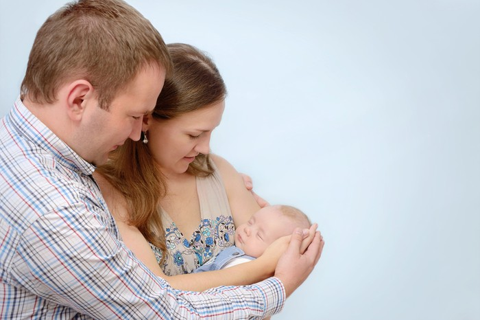 A married couple cradling their newborn baby.