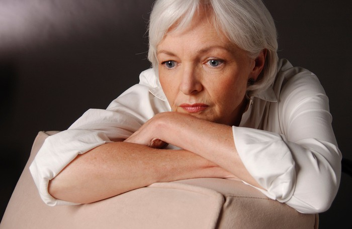 A clearly worried senior woman resting her crossed arms on the back of a chair, and her head on her forearms.