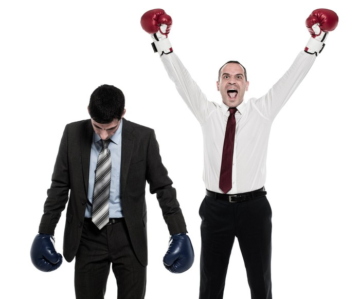 Two men in business attire are wearing boxing gloves. One has his head lowered, while the other has his arms raised in celebration.