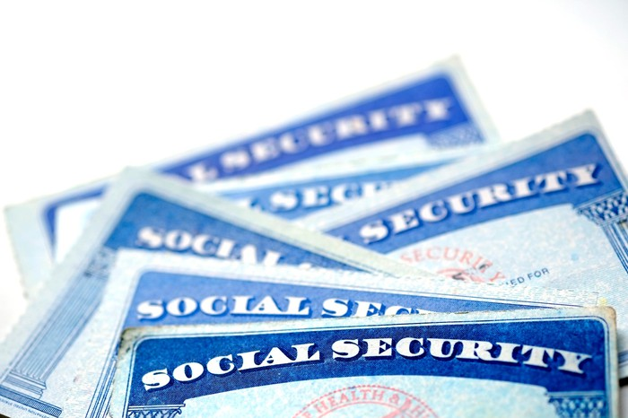 A half-dozen Social Security cards stacked in a messy pile atop one another.