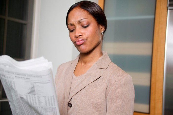 A skeptical woman smirking as she closely reads the financial section of a newspaper.