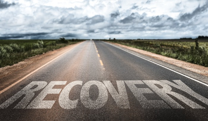"A deserted road with the word ""recovery"" written across it in all caps."