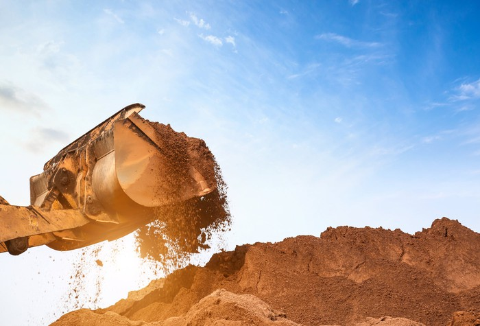 Earth-moving equipment moving sand from a big pile