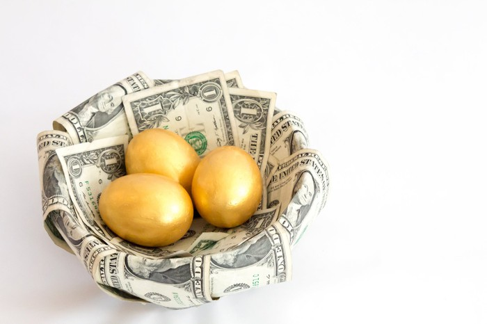 A basket covered in dollar bills that contains three golden eggs.