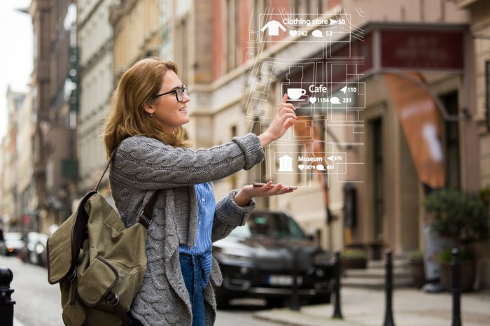 A woman uses a pair of AR glasses on the street.
