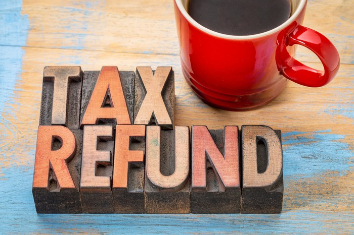 "The words ""tax refund"" spelled out in gold letters on wooden blocks next to a red mug of coffee."