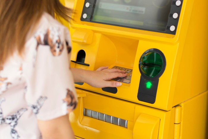 Woman withdrawing funds from a bright yellow ATM machine.