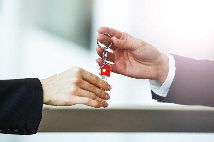 A person handing another person keys to a home.