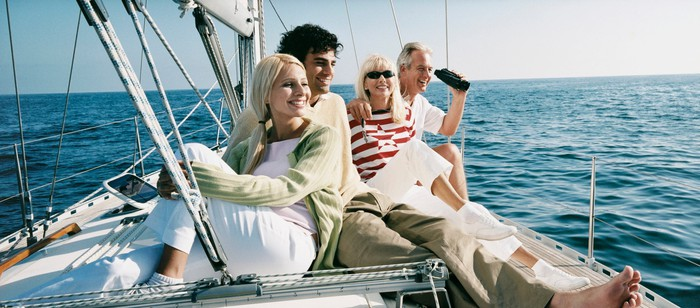 Four people on a sailboat at sea.
