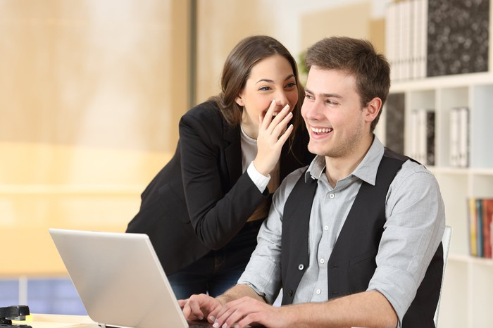Young woman whispering into the ear of a male colleague. Both of them are smiling from ear to ear.