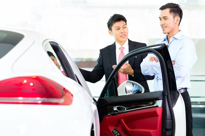Two Asian men talk next to a car.