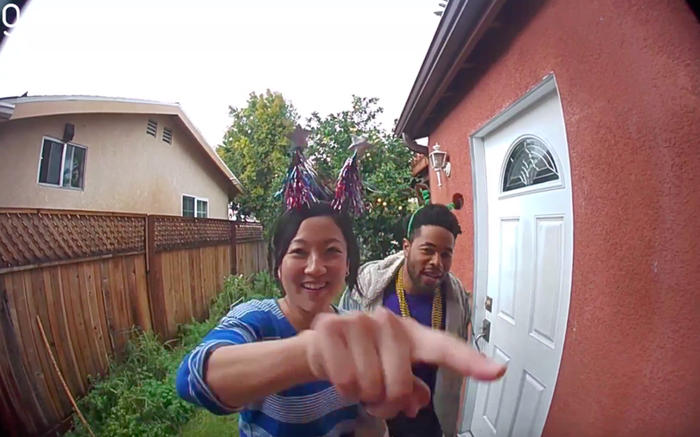 A picture of two people on a doorstep with one about the ring the doorbell.