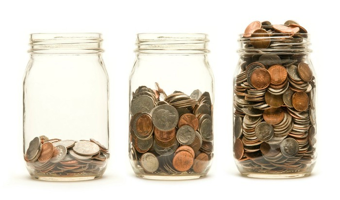 Three change jars filled with an increasing number of coins.