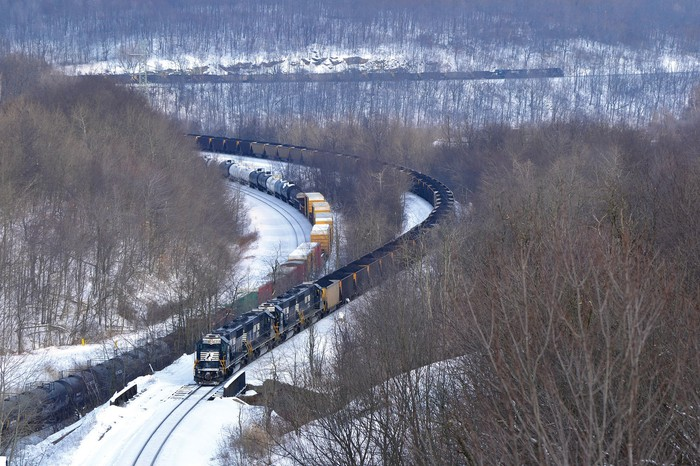 Norfolk Southern trains snake through a snow-covered mountain pass.