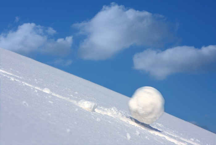 A snowball tumbles downhill and speeds up.