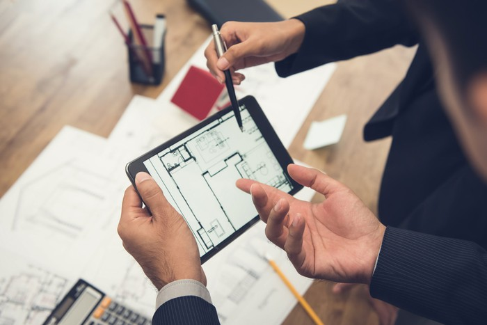 Two people looking at a blueprint on a tablet.