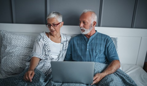 senior couple in bed with laptop_GettyImages-935818702