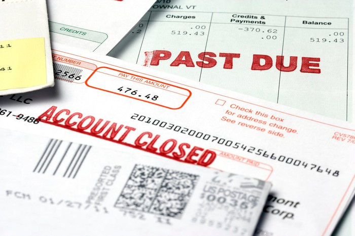 """Stack of bills labeled """"past due"""" and """"account closed."""""""