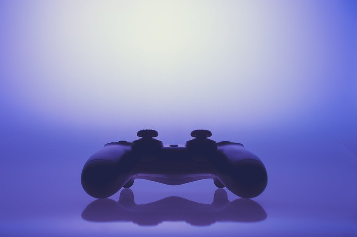 A black video game controller set against a purple background.
