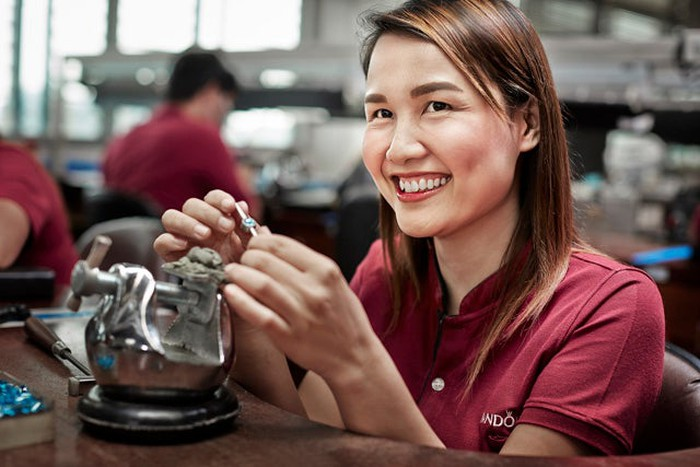 A Pandora worker smiles as she works on assembling a charm.