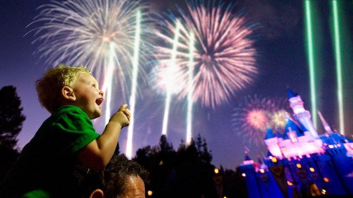 Young boy on man's shoulders watching fireworks with Cinderella's Castle in background.