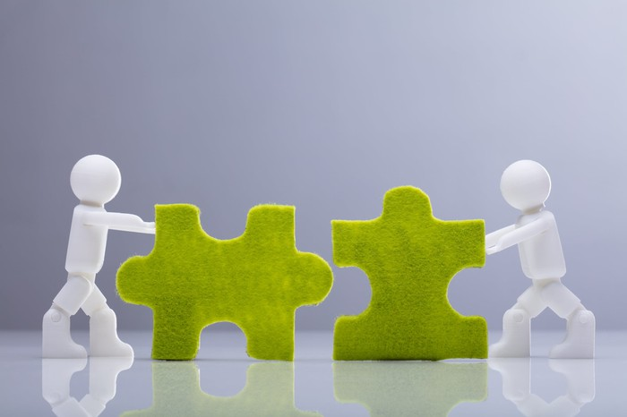 Two miniature human figurines pushing together two green jigsaw puzzle pieces.