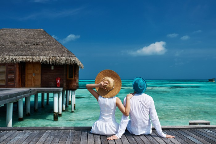 A couple sitting on a wooden walkway looks out over the ocean, with thatch-roof villa to the left