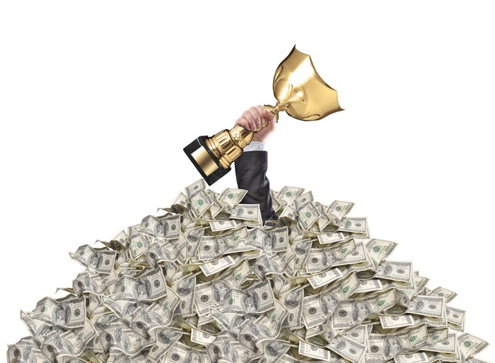 A man's arm holding a gold trophy sticking up through a pile of cash.