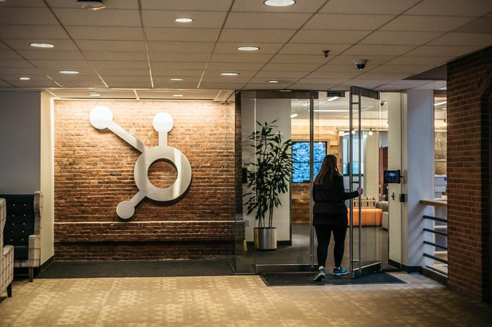 HubSpot's logo on a brown brick wall and a woman opening the glass door next to it.