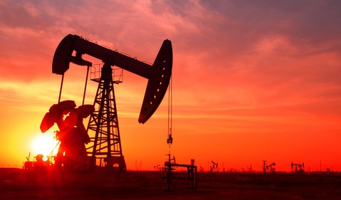 A silhouette of an oil pump in an oil field at sunset