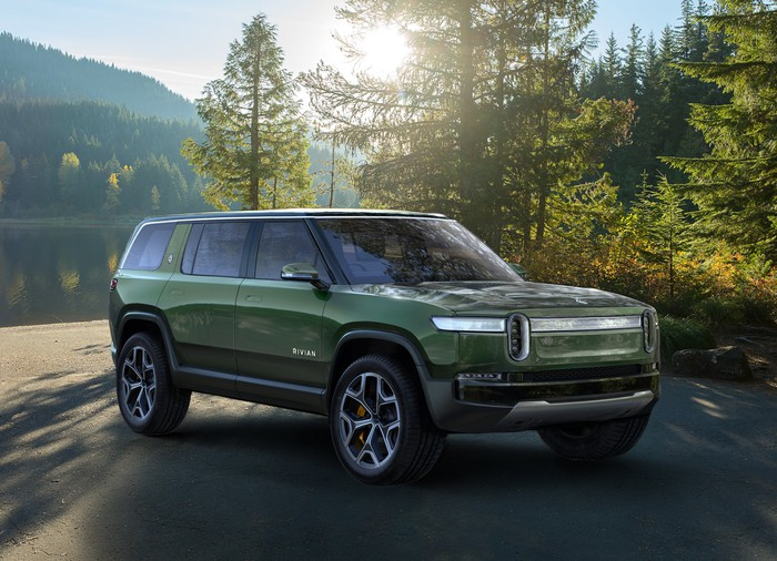 A green Rivian R1S, an upscale electric 7-passenger SUV.