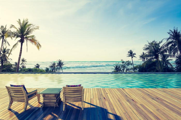 Swimming pool in tropics with ocean in the background.