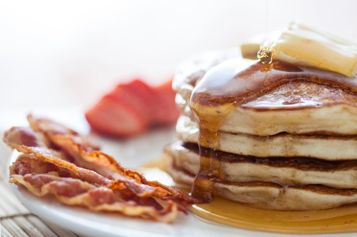 A stack of pancakes with butter and syrup and a side of bacon.
