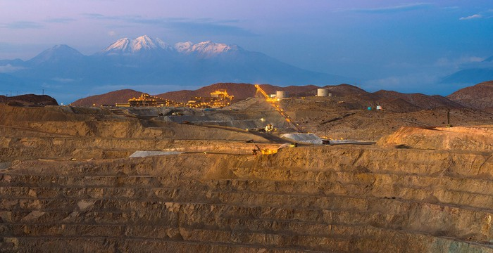 Open-pit mining operation with equipment near the top of the mine, with mountains in the background.