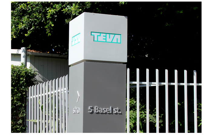 Sign with Teva logo and address, next to a fence and vegetation
