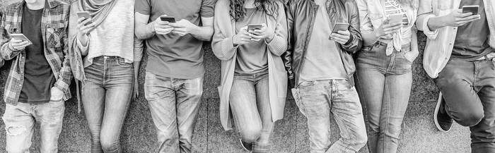 A black and white image of several millennials on their smartphones.