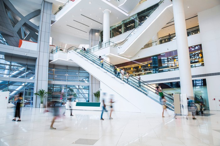 An interior view of a busy multilevel mall with a lot of shoppers.