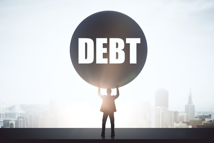 Man holding up large ball with the word debt on it